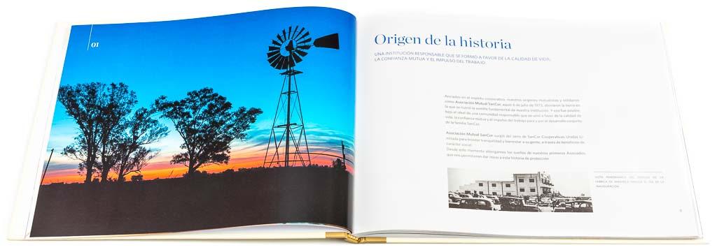 Doble página de apertura de un capítulo del libro institucional Sancor Salud aniversario 40 años, con una fotografía en alta resolución de un molino de viento al anochecer del Banco de imágenes de Marco Guoli