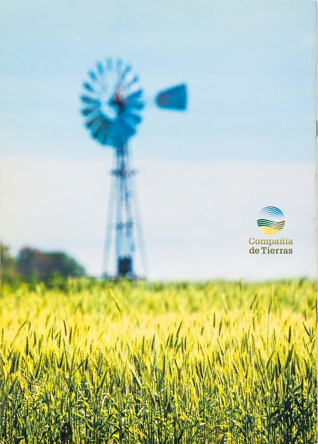 Contra tapa del Folleto institucional Compañia de tierras con una imagen de un molino de viento desenfocado y un cultivo de trigo del Banco de imágenes de Marco Guoli