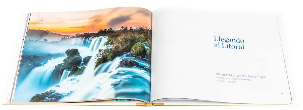 Doble página de apertura de un capítulo del libro institucional Sancor Salud aniversario 40 años, con una fotografía en alta resolución de las cataratas del Iguazú al amanecer del Banco de imágenes de Marco Guoli